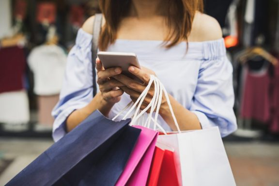 Woman with shopping bags looking at cellphone