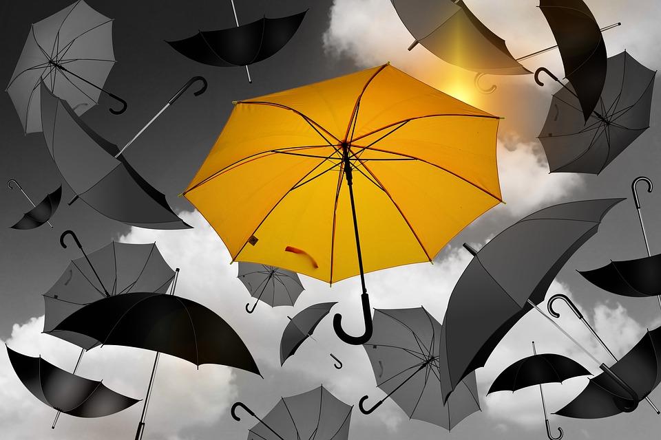 yellow umbrella in sea of black and white umbrellas