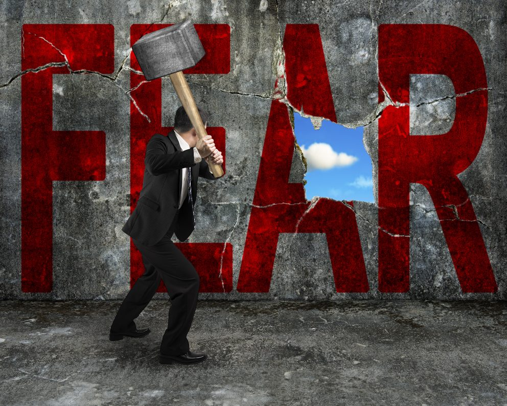 businessman holding hammer to the word fear written on a wall